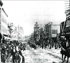 A parade on the 300 block of S. Elm St circa 1900